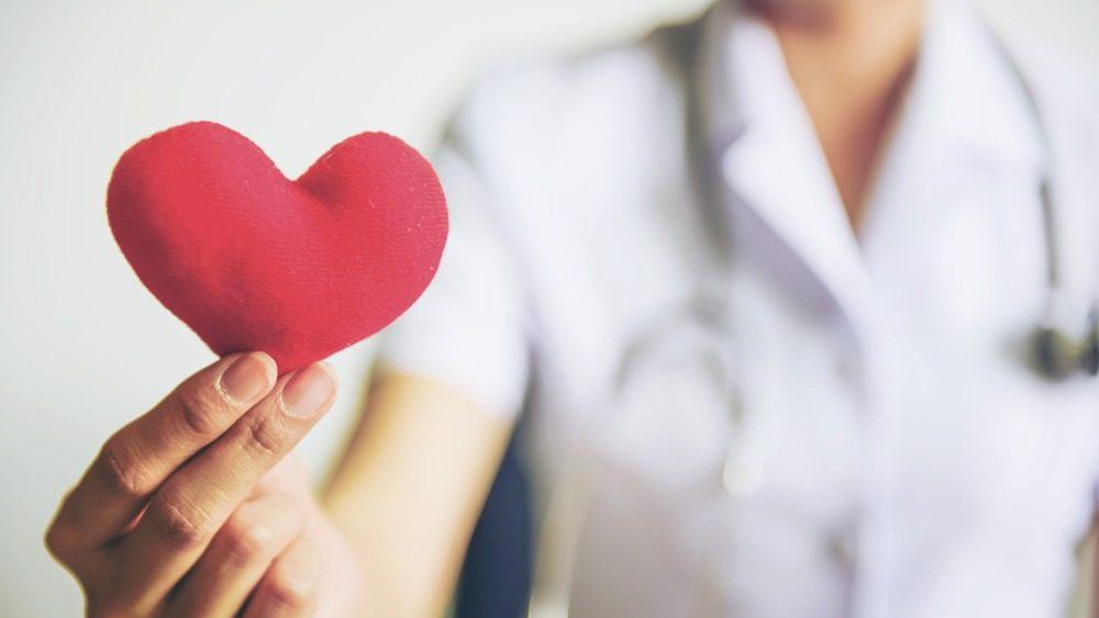enfermera actual sosteniendo un corazón rojo de salud